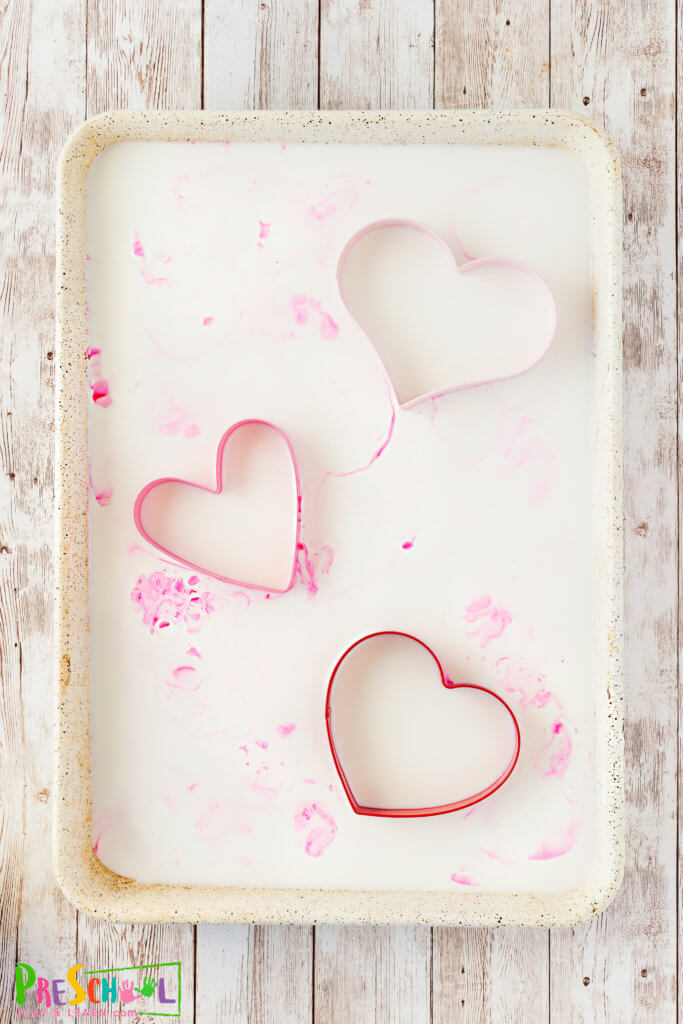 set-up the valentines day science experiment by pourig milk in a container and adding herat valentines day cookie cutters