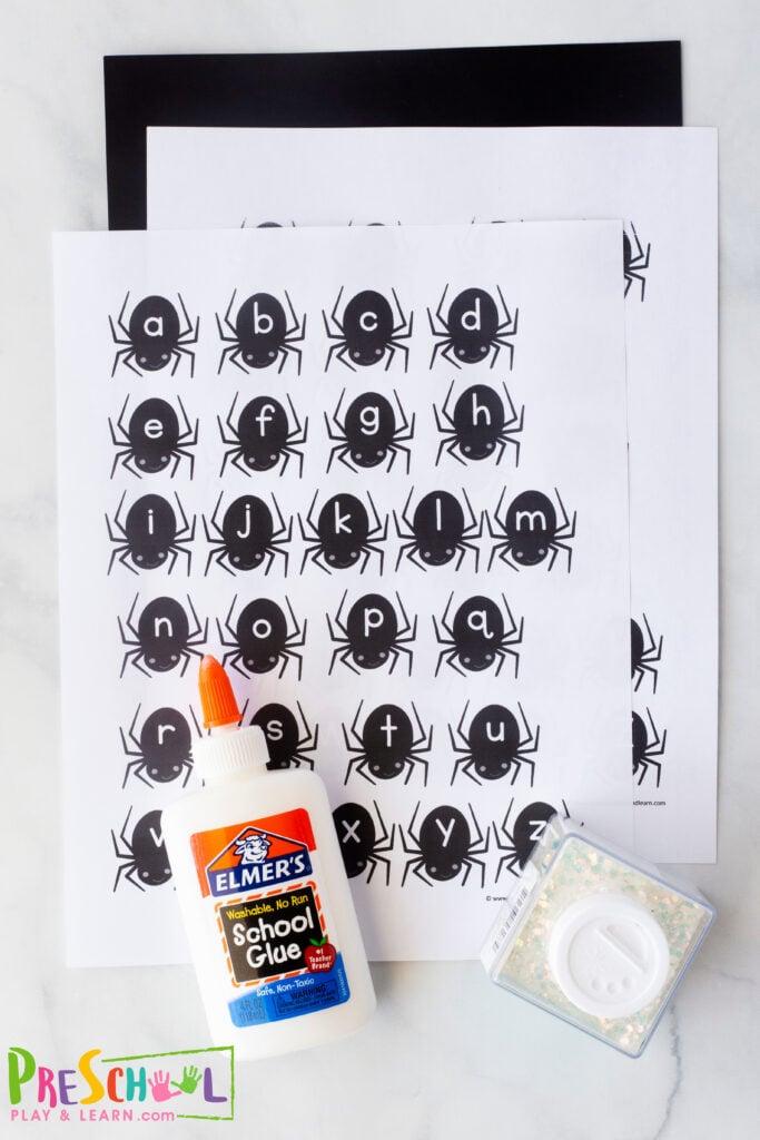 black construction paper liquid glue glitter - we suggest white, green, and purple letter spider printable (template below) scissors